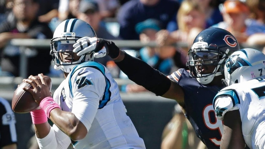 Carolina Panthers' Cam Newton, left, looks to pass under pressure from Chicago Bears' Willie Young, right, during the second half of an NFL football game in Charlotte, N.C., Sunday, Oct. 5, 2014. (AP Photo/Bob Leverone)