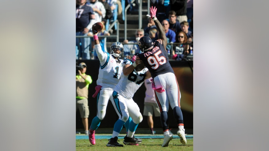 Carolina Panthers' Cam Newton (1) throws a pass as Chicago Bears' Ego Ferguson (95) defends during the second half of an NFL football game in Charlotte, N.C., Sunday, Oct. 5, 2014. The Panthers won 31-24. (AP Photo/Mike McCarn)