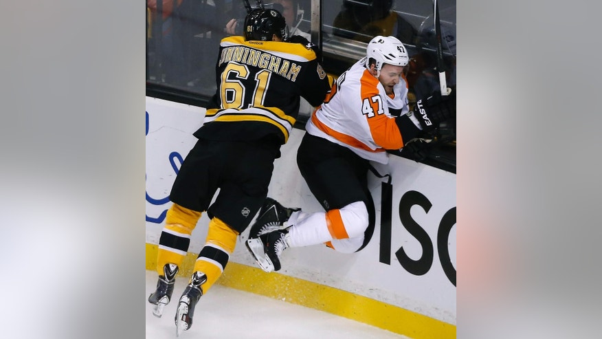 Boston Bruins left wing Craig Cunningham (61) checks Philadelphia Flyers defenseman Andrew MacDonald (47) into the boards in the first period of an NHL hockey game in Boston, Wednesday, Oct. 8, 2014. (AP Photo/Elise Amendola)