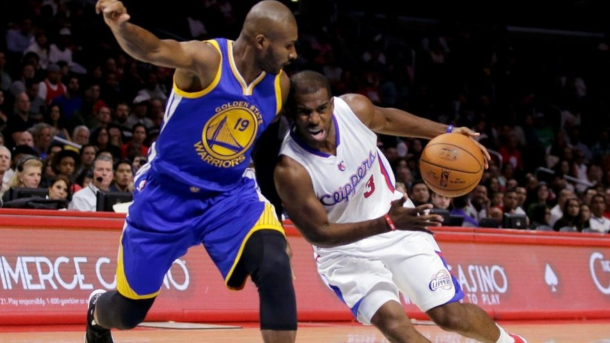 Los Angeles Clippers guard Chris Paul, right, drives around Golden State Warriors guard Leandro Barbosa during the first half of an NBA basketball preseason game in Los Angeles, Tuesday, Oct., 7, 2014. (AP Photo/Chris Carlson)