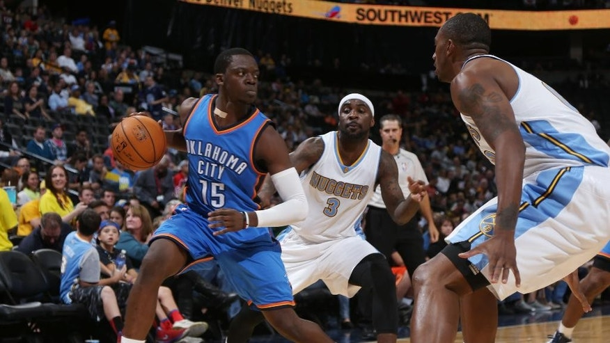 From left, Oklahoma City Thunder guard Reggie Jackson works ball inside for shot as Denver Nuggets guard Ty Lawson and forward Darrell Arthur cover in the first quarter of an NBA exhibition basketball game in Denver on Wednesday, Oct. 8, 2014. (AP Photo/David Zalubowski)