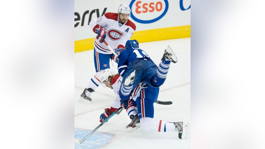 Toronto Maple Leafs' Joffrey Lupul, right, collides with Montreal Canadiens' Tom Gilbert as Canadiens' teammate Andrei Markov looks on during first period NHL hockey action in Toronto on Wednesday, Oct. 8, 2014. (AP Photo/The Canadian Press, Darren Calabrese)