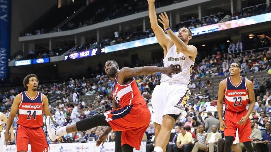 New Orleans Pelicans' Ryan Anderson (33) shoots over Washington Wizards' DeJuan Blair (45) during the first half of an NBA preseason basketball game in Jacksonville, Fla., Wednesday, Oct. 8, 2014. (AP Photo/Gary McCullough)