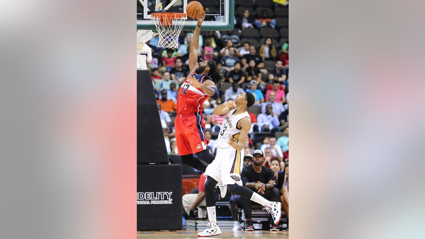 Washington Wizards' Nene (42) lays up the ball past New Orleans Pelicans' Anthony Davis (23) during the first half of an NBA preseason basketball game in Jacksonville, Fla., Wednesday, Oct. 8, 2014. (AP Photo/Gary McCullough)