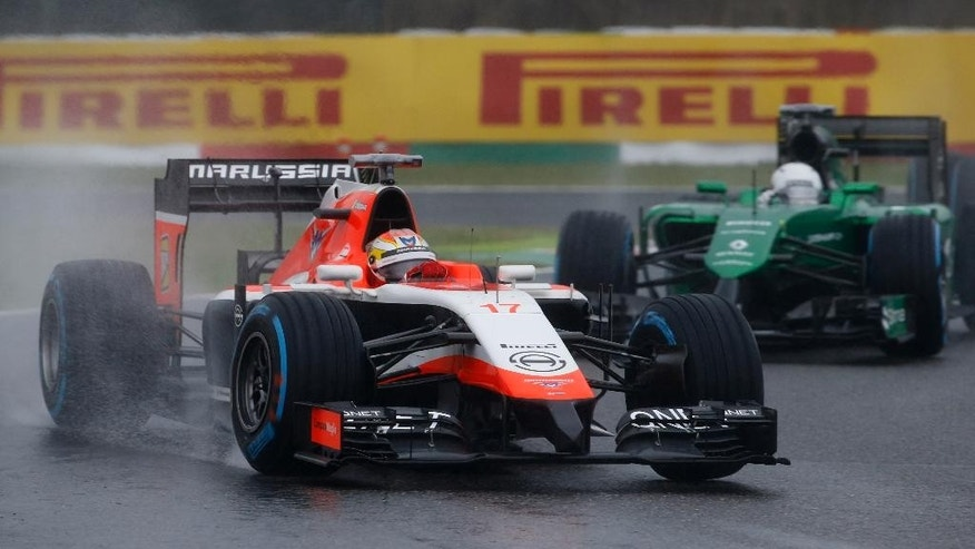 Marussia driver Jules Bianchi of France leads Caterham driver Kamui Kobayashi of Japan during the Japanese Formula One Grand Prix at the Suzuka Circuit in Suzuka, central Japan, Sunday, Oct. 5, 2014. Bianchi has been taken to hospital and is unconscious following a crash during the race. (AP Photo/Toru Takahashi)