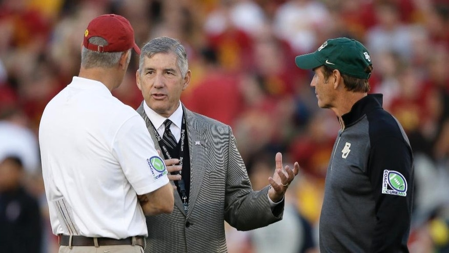 FILE- In this Sept. 27, 2014, file photo, Big 12 Conference Commissioner Bob Bowlsby, center, talks with Iowa State coach Paul Rhoads, left, and Baylor coach Art Briles before an NCAA college football game in Ames, Iowa. The Big 12 has publicly reprimanded and fined Iowa State athletic director Jamie Pollard $25,000 for his rant against league officiating.  (AP Photo/Charlie Neibergall)