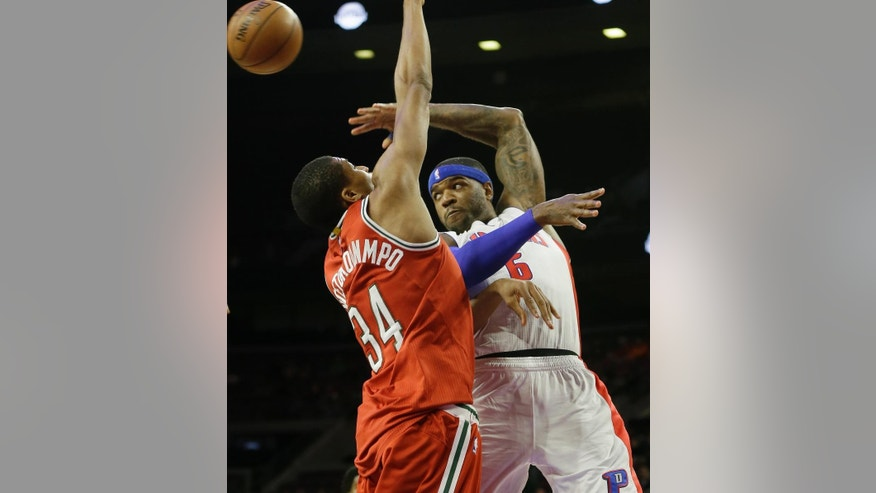 Detroit Pistons forward Josh Smith (6) passes the ball defended by Milwaukee Bucks guard Giannis Antetokounmpo (34) of Greece, during the first half of an NBA basketball game in Auburn Hills, Mich., Thursday, Oct. 9, 2014. (AP Photo/Carlos Osorio)