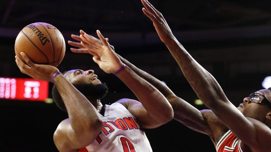 Milwaukee Bucks center Larry Sanders, right, reaches in on Detroit Pistons center Andre Drummond (0) during the first half of an NBA basketball game in Auburn Hills, Mich., Thursday, Oct. 9, 2014. (AP Photo/Carlos Osorio)