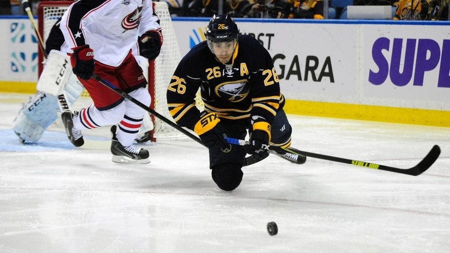 Columbus Blue Jackets defenseman Jack Johnson (7) gives chase to Buffalo Sabres left winger Matt Moulson (26) as Moulson battles for the puck during the first period of an NHL hockey game season opener, Thursday, Oct., 9, 2014, in Buffalo, N.Y. (AP Photo/Gary Wiepert)