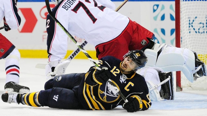 Columbus Blue Jackets goaltender Sergei Bobrovsky (72), of Russia, gets checked by Buffalo Sabres right winger Brian Gionta (12), as he falls into the goal crease during the first period of an NHL hockey game season opener, Thursday, Oct., 9, 2014, in Buffalo, N.Y. (AP Photo/Gary Wiepert)