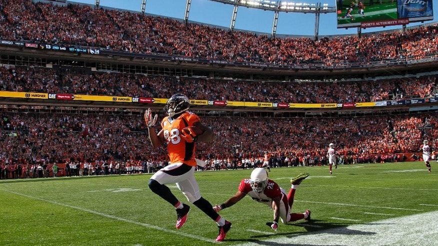 Denver Broncos wide receiver Demaryius Thomas (88) runs in a touchdown pass as Arizona Cardinals free safety Rashad Johnson (26) falls during the first half of an NFL football game, Sunday, Oct. 5, 2014, in Denver. (AP Photo/Joe Mahoney)