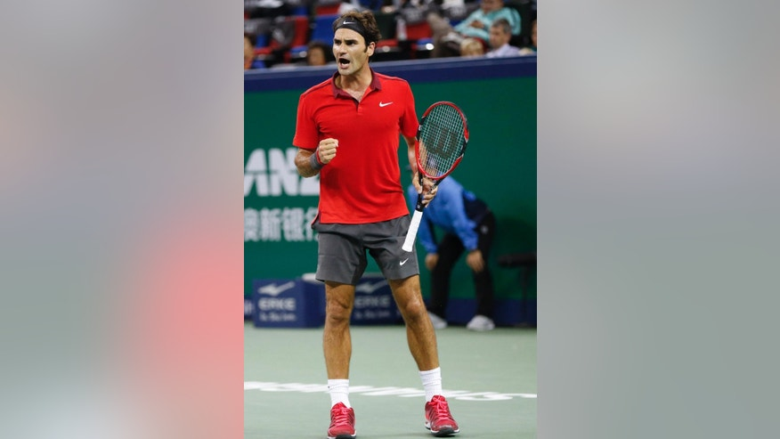 Roger Federer of Switzerland reacts after score a point during match against  Roberto Bautista Agut of Spain during their men's singles third round match at the Shanghai Masters Tennis Tournament in Shanghai, China, Thursday, Oct. 9, 2014.  (AP Photo/Vincent Thian)