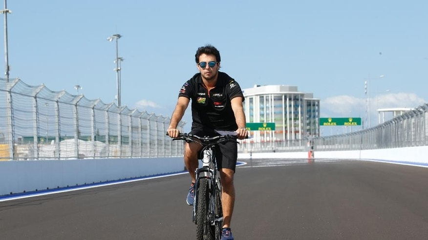 Force India driver Sergio Perez of Mexico rides a bicycle as he inspect the Sochi Autodrom Formula One circuit in Sochi, Russia, Thursday, Oct. 9, 2014. The inaugural Russian GP will be held on Sunday in Sochi, the Black Sea resort that hosted this year's Winter Olympics. (AP Photo/Luca Bruno)
