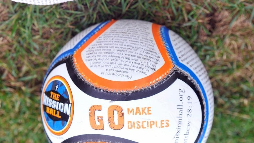 In this Oct. 6, 2014, photo, the Mission Ball rests next to the bench while the Haitian national women's soccer team practices in South Bend, Ind. Upon getting word that the Trinidad and Tobago women's national soccer team was in dire financial straits, Haiti's team took a look at its fundraising for World Cup qualifying and decided to turn it over to the competition. (AP Photo/Joe Raymond)
