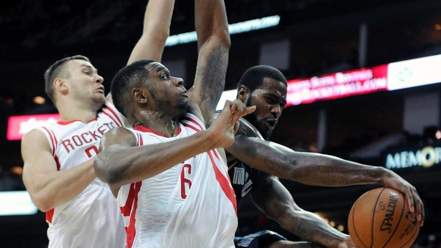 Memphis Grizzlies' Earl Clark, right, passes the ball around Houston Rockets Donatas Motiejunas, left, and Kostas Papanikolaou in the second half of an NBA exhibition basketball game Thursday, Oct. 9, 2014, in Houston. (AP Photo/Pat Sullivan)