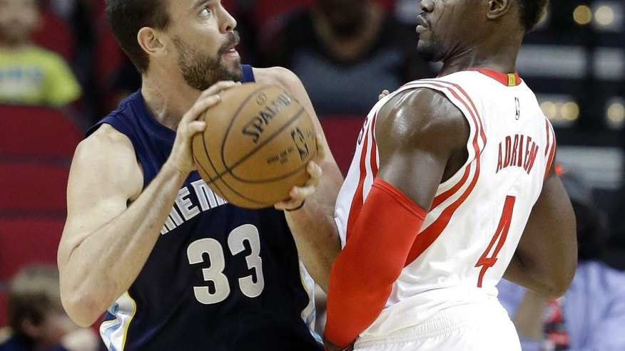 Memphis Grizzlies' Marc Gasol (33) pushes Houston Rockets' Jeff Adrien (4) in the first half of an NBA exhibition basketball game Thursday, Oct. 9, 2014, in Houston. (AP Photo/Pat Sullivan)