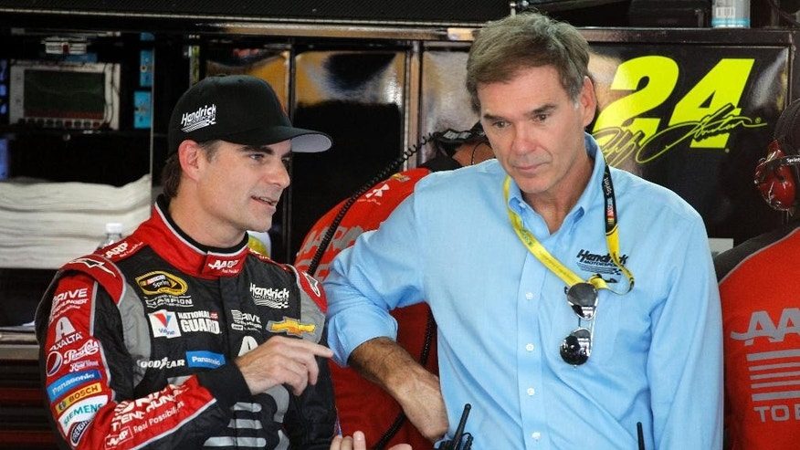Jeff Gordon, left, talks with Ray Evernham, right, during practice for Saturday's NASCAR Bank of America Sprint Cup series auto race in Concord, N.C., Thursday, Oct. 9, 2014. (AP Photo/Terry Renna)