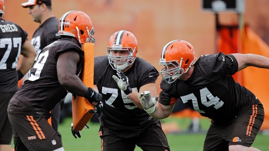 Cleveland Browns guard Joel Bitonio (75) and tackle Paul McQuistan (74) block against offensive tackle Vinston Painter during practice at the NFL football team's facility in Berea, Ohio Wednesday, Oct. 8, 2014. (AP Photo/Mark Duncan)