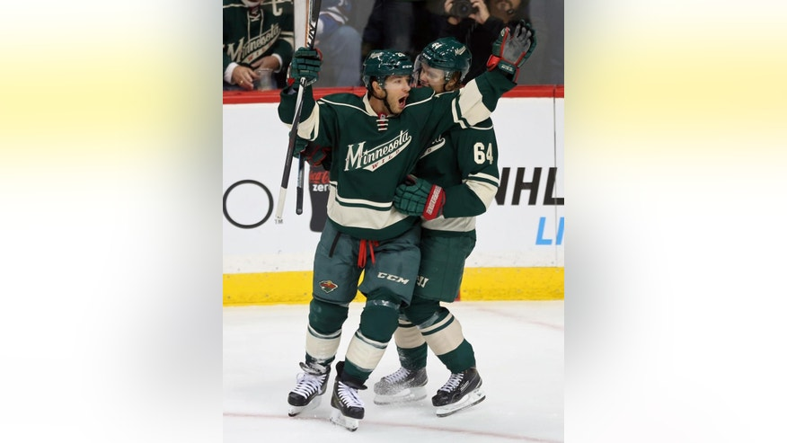 Minnesota Wild's Jason Pominville, left, and Mikael Granlund, of Finland, celebrate Pominville's goal off Colorado Avalanche goalie Semyon Varlamov, of Russia, in the first period of an NHL hockey game, Thursday, Oct. 9, 2014, in St. Paul, Minn. (AP Photo/Jim Mone)