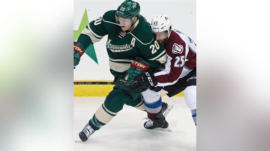 Colorado Avalanche's Maxime Talbot, right, attempts to slow up Minnesota Wild's Ryan Suter in a race for the puck in the first period of an NHL hockey game, Thursday, Oct. 9, 2014, in St. Paul, Minn. (AP Photo/Jim Mone)