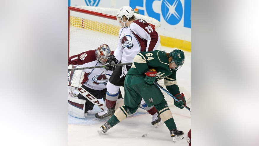 Colorado Avalanche goalie Semyon Varlamov, left, of Russia, and Nathan MacKinnon join Minnesota Wild's Mikael Granlund, right, of Finland, in a search for the puck in the first period of an NHL hockey game, Thursday, Oct. 9, 2014, in St. Paul, Minn. (AP Photo/Jim Mone)