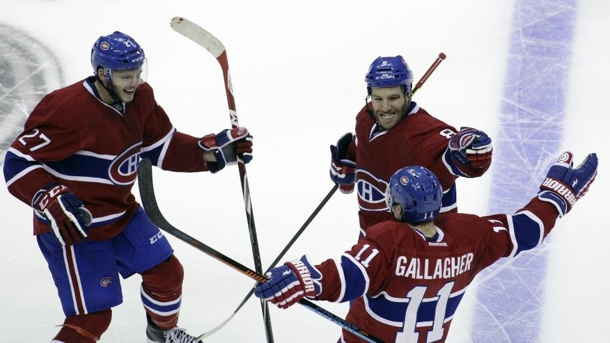 Montreal Canadiens' Brendan Gallagher (11) celebrates with teammates Alex Galchenyuk (27) and Brandon Prust (8) after he scored the winning goal in a shootout against the Washington Capitals during an NHL hockey game, Thursday, Oct 9, 2014, in Washington. The Canadiens won 2-1 in a shootout.(AP Photo/Luis M. Alvarez)