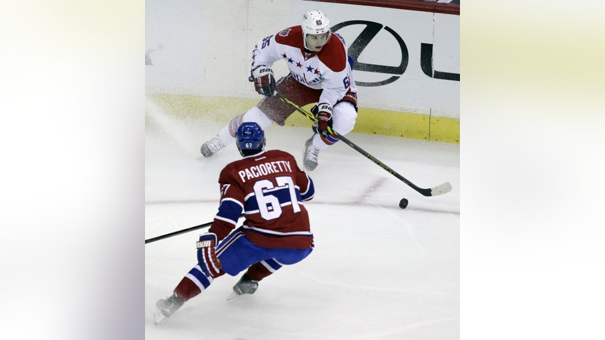 Washington Capitals' Andre Burakovsky, top, moves the puck on Montreal Canadiens' Max Pacioretty (67) during the first period of an NHL hockey game, Thursday, Oct 9, 2014, in Washington. (AP Photo/Luis M. Alvarez)