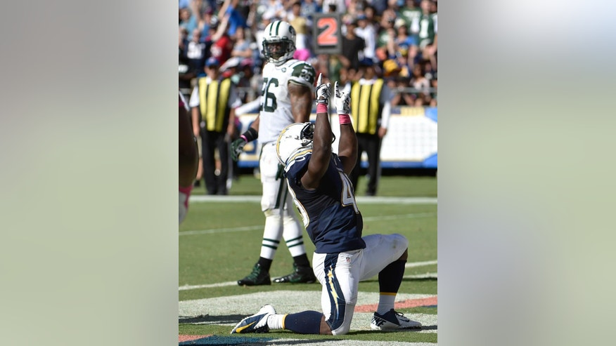 San Diego Chargers running back Branden Oliver celebrates a touchdown as New York Jets strong safety Dawan Landry looks on during the second half of an NFL football game, Sunday, Oct. 5, 2014, in San Diego. (AP Photo/Denis Poroy)