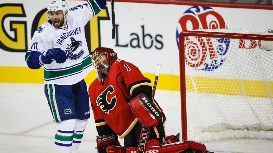Vancouver Canucks' Chris Higgins, left, celebrates his team's goal as Calgary Flames goalie Jonas Hiller, from Switzerland, picks himself up during first period NHL hockey action in Calgary, Alberta, Wednesday, Oct. 8, 2014.  (AP Photo/The Canadian Press, Jeff McIntosh)