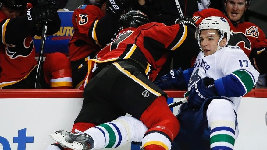 Vancouver Canucks' Radim Vrbata, right, is checked into the boards Calgary Flames' Lance Bouma during second period NHL hockey action in Calgary, Alberta, Wednesday, Oct. 8, 2014.  (AP Photo/The Canadian Press, Jeff McIntosh)