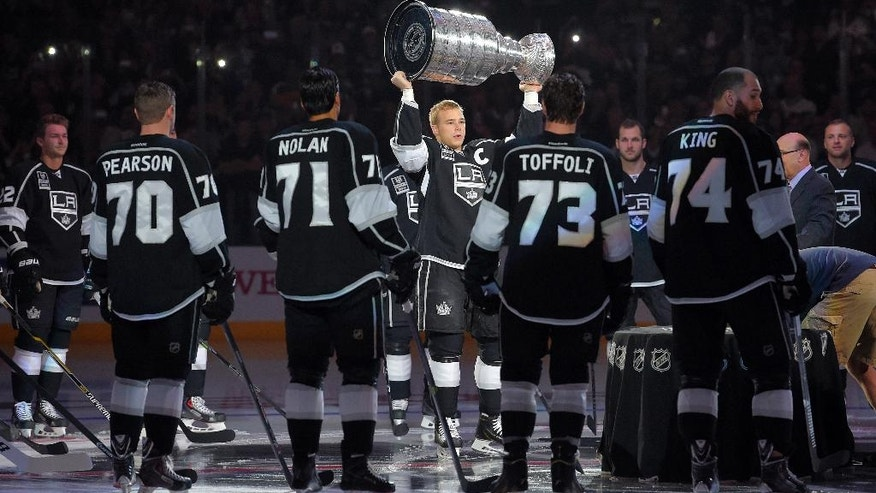 Los Angeles Kings right wing Dustin Brown, center, raises the Stanley Cup before the Stanley Cup Championship banner is revealed prior to an NHL hockey game against the San Jose Sharks, Wednesday, Oct. 8, 2014, in Los Angeles. (AP Photo/Mark J. Terrill)