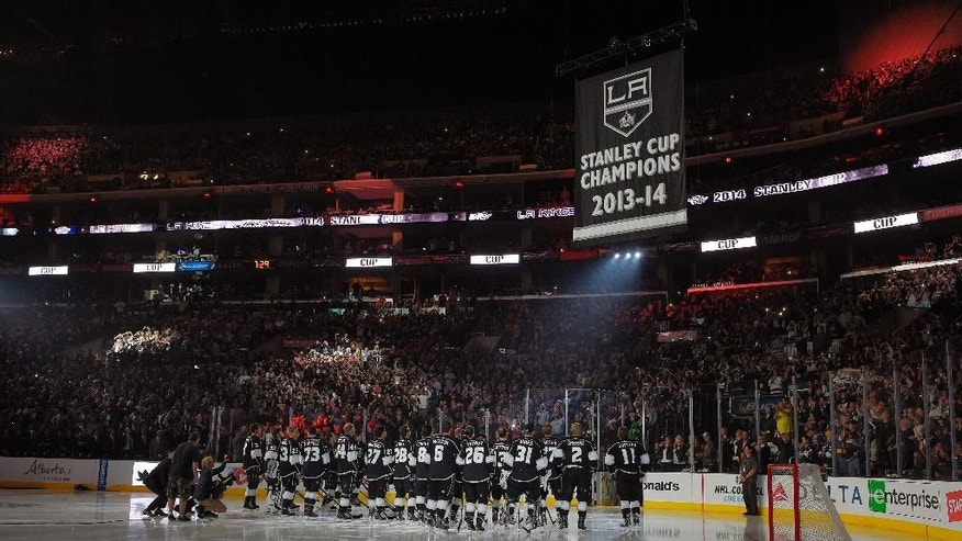 Members of the Los Angeles Kings watch as their second Stanley Cup Championship banner is raised prior to an NHL hockey game against the San Jose Sharks, Wednesday, Oct. 8, 2014, in Los Angeles. (AP Photo/Mark J. Terrill)