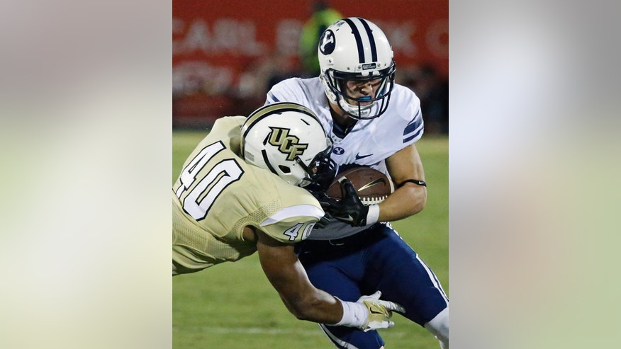 Brigham Young wide receiver Mitchell Juergens, right, is stopped by Central Florida linebacker Chequan Burkett (40) after a reception during the first half of an NCAA college football game in Orlando, Fla., Thursday, Oct. 9, 2014. (AP Photo/John Raoux)