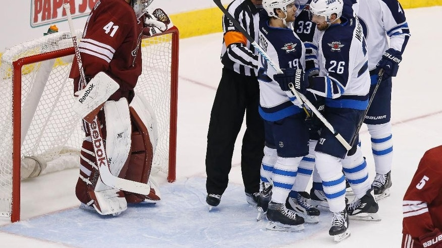 Arizona Coyotes' Mike Smith (41) dejectedly stands in front of the net as Winnipeg Jets' Dustin Byfuglien (33) celebrates his goal with teammates Jim Slater (19), Blake Wheeler (26) and Paul Postma (4) as referee Dan O'Rourke (9) keeps the players away from the goalie during the second period of an NHL hockey game Thursday, Oct. 9, 2014, in Glendale, Ariz.  The Jets defeated the Coyotes 6-2. (AP Photo/Ross D. Franklin)
