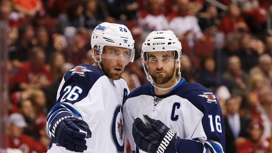 Winnipeg Jets' Blake Wheeler (26) talks with Jets' Andrew Ladd (16) during a break in the action in the first period of an NHL hockey game against the Arizona Coyotes Thursday, Oct. 9, 2014, in Glendale, Ariz. (AP Photo/Ross D. Franklin)