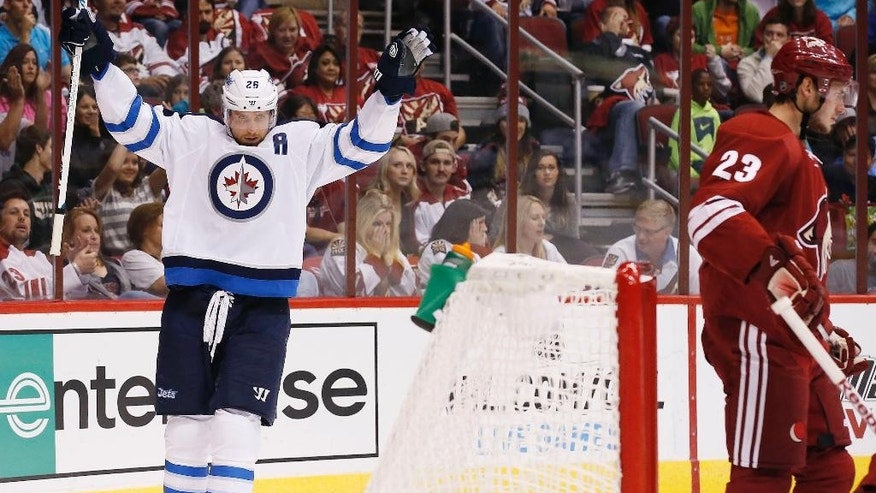 Winnipeg Jets' Blake Wheeler (26) celebrates his goal, the first of two during the first period, against the Arizona Coyotes as Coyotes' Oliver Ekman-Larsson (23), of Sweden, skates in front of the goal area in an NHL hockey game Thursday, Oct. 9, 2014, in Glendale, Ariz. (AP Photo/Ross D. Franklin)