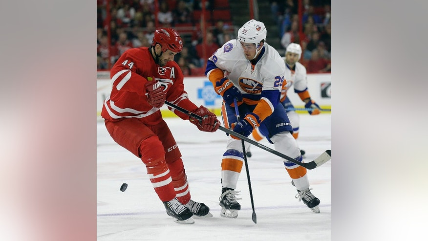 New York Islanders' Brock Nelson (29) and Carolina Hurricanes' Jay Harrison (44) chase the puck during the first period of an NHL hockey game in Raleigh, N.C., Friday, Oct. 10, 2014. (AP Photo/Gerry Broome)
