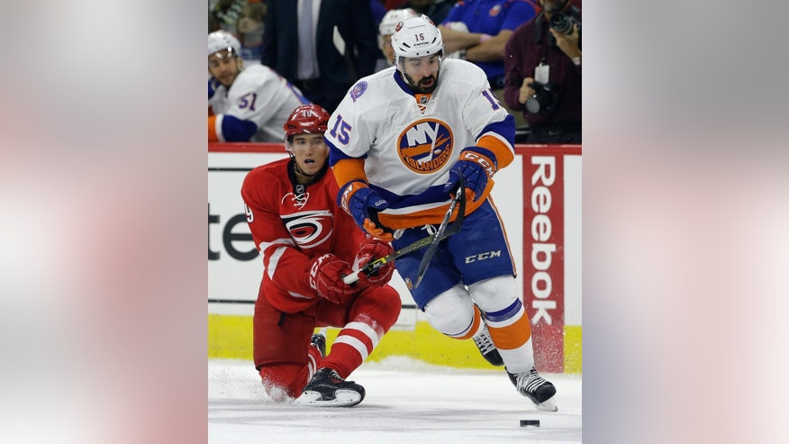 New York Islanders' Cal Clutterbuck (15) and Carolina Hurricanes' Victor Rask (49), of Sweden, chase the puck during the first period of an NHL hockey game in Raleigh, N.C., Friday, Oct. 10, 2014. (AP Photo/Gerry Broome)