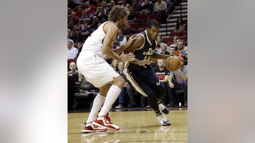 Utah Jazz center Derrick Favors, right, drives on Portland Trail Blazers center Robin Lopez during the first half of a pre-season NBA basketball game in Portland, Ore., Thursday, Oct. 9, 2014.(AP Photo/Don Ryan)