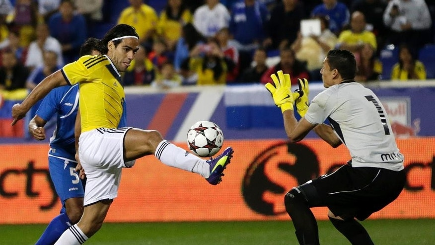 Colombia's Falcao Garcia, center, kicks the ball as El Salvador goalkeeper Henry Hernandez, right, and Alexander Mendoza, back, defend during the second half of an international soccer friendly match at Red Bull Arena, Friday, Oct. 10, 2014, in Harrison, N.J. (AP Photo/Julio Cortez)