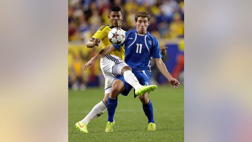 Colombia's Alexander Mejia, left, and El Salvador's Pablo Punyed  compete for the ball during the second half of an international soccer friendly match at Red Bull Arena, Friday, Oct. 10, 2014, in Harrison, N.J. Colombia won 3-0. (AP Photo/Julio Cortez)
