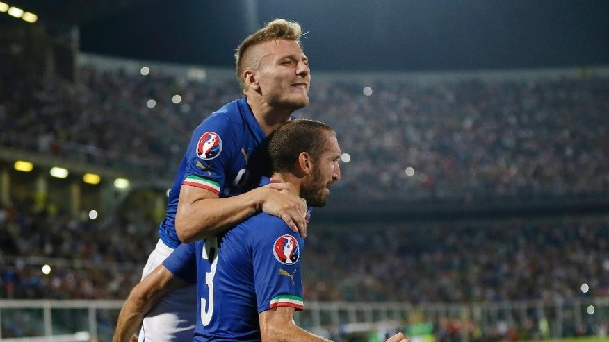 Italy's Giorgio Chiellini, bottom, celebrates with his teammate Italy's Ciro Immobile after scoring during the Euro 2016 qualifying soccer match between Italy and Azerbaijan, at the La Favorita stadium, in Palermo, Italy, Friday, Oct. 10, 2014. (AP Photo/Antonio Calanni)
