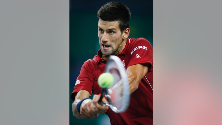 Novak Djokovic of Serbia returns a shot against David Ferrer of Spain during their men's singles quarterfinal match of Shanghai Masters Tennis Tournament in Shanghai, China, Friday, Oct. 10, 2014.  (AP Photo/Vincent Thian)