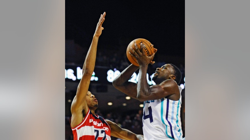Charlotte Hornets forward Michael Kidd-Gilchrist (14) looks to shoot as Washington Wizards forward Otto Porter Jr. (22) defends during the first half of a preseason NBA basketball game, Friday, Oct. 10, 2014, in Greenville, S.C. (AP Photo/Rainier Ehrhardt)