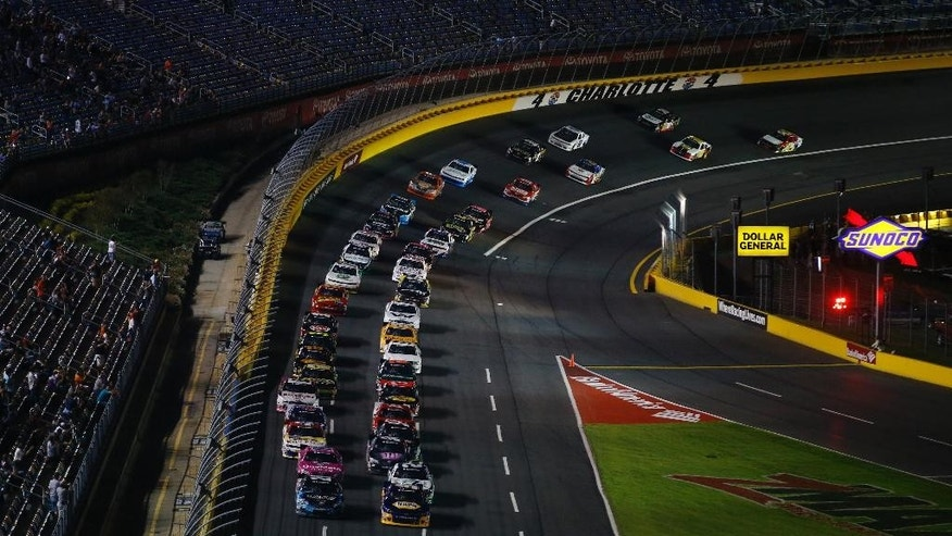 Drivers make their way out of Turn 4 at the start of the NASCAR Nationwide series Drive for the Cure 300 auto race at Charlotte Motor Speedway in Concord, N.C., Friday, Oct. 10, 2014. (AP Photo/Chris Keane)