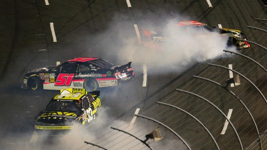 Ty Dillon, right, spins out of control as Jeremy Clements (51) and Cale Conley (33) also lose control of their cars while heading into Turn 1 during the NASCAR Nationwide series Drive for the Cure 300 auto race at Charlotte Motor Speedway in Concord, N.C., Friday, Oct. 10, 2014. (AP Photo/Chris Keane)