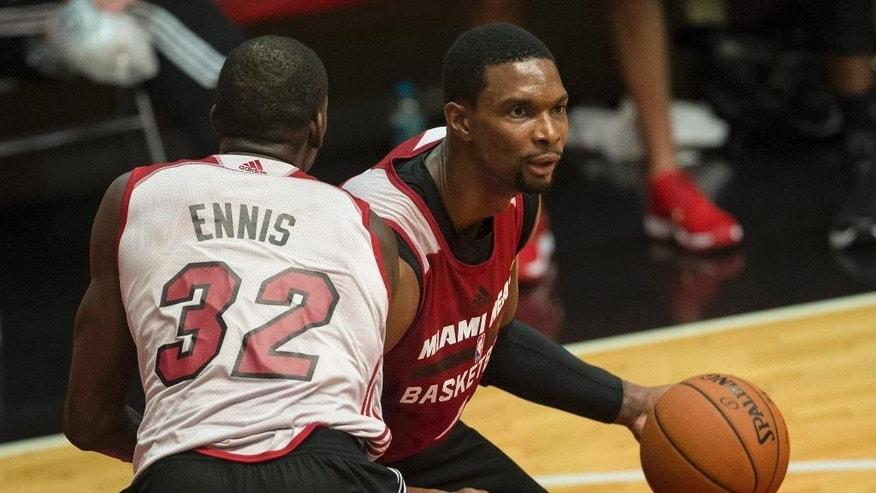 Miami Heat's Chris Bosh, right, moves around teammate James Ennis as they train in Rio de Janeiro, Brazil, Friday, Oct. 10, 2014. The Miami Heat will play the Cleveland Cavaliers in a preseason game on Saturday as part of the NBA Global Games. (AP Photo/Felipe Dana)