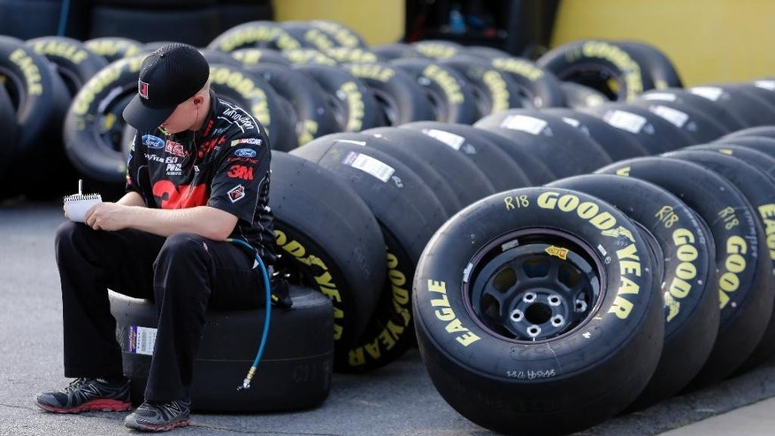 Alex Cunningham, a trie specialist for driver Greg Biffle's team, makes note as he sits on a Goodyear race tire before practice for Saturday's NASCAR Bank of America Sprint Cup series auto race at Charlotte Motor Speedway in Concord, N.C., Friday, Oct. 10, 2014. (AP Photo/Chuck Burton)