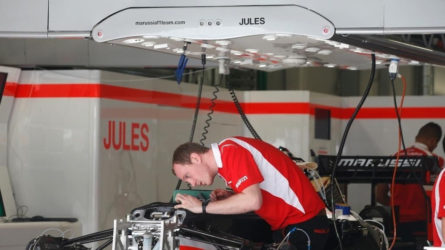 A Marussia mechanic works on a car in the Jules Bianchi garage at the Sochi Autodrom Formula One circuit , in Sochi, Russia, Thursday, Oct. 9, 2014.  Formula One drivers say they will race this weekend's Russia Grand Prix for Jules Bianchi, who was seriously injured in an accident last week in Japan. In Japan, Bianchi is in critical but stable condition after suffering a severe head injury when his Marussia car ploughed into a recovery crane at the Suzuka course during rainy conditions. The inaugural Russian GP will be held on Sunday in Sochi, the Black Sea resort that hosted this year's Winter Olympics. (AP Photo/Luca Bruno)