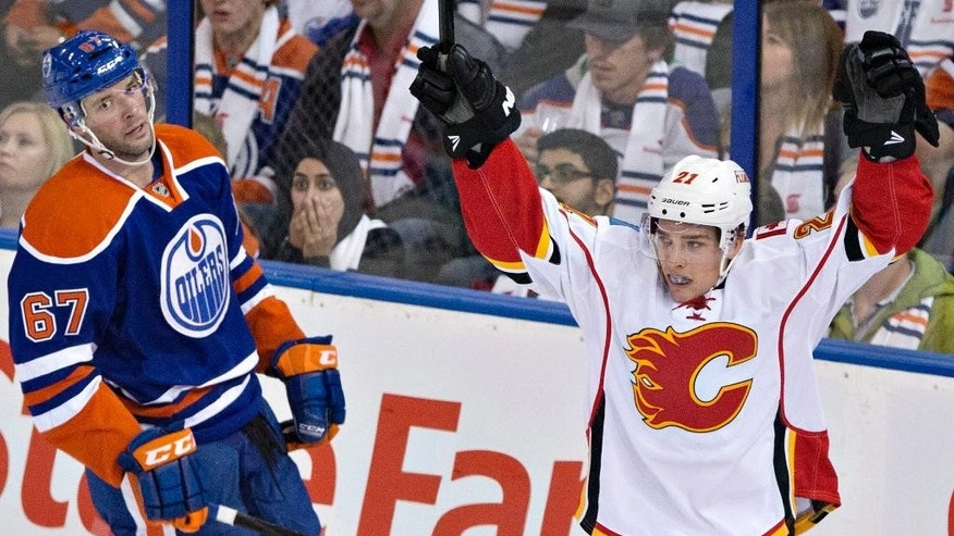 Calgary Flames' Mason Raymond (21) celebrates a goal as Edmonton Oilers' Benoit Pouliot (67) looks on during third period NHL hockey action in Edmonton, Alberta, on Thursday Oct.9, 2014. (AP Photo/The Canadian Press, Jason Franson)